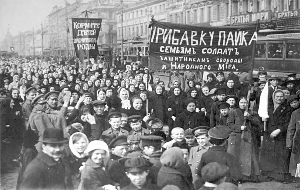 Demonstration from 1917. Women and  men hold banners with Cyrillic writing. The street is crowded. There are children in the foreground.