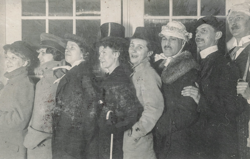 Black and white photograph. Women pose in men's clothes and hats. Men pose in women's hats and coats. They stand in a line with cheerful expressions.