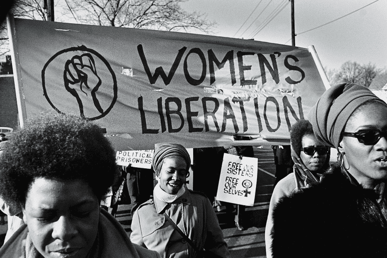 Women walk before a large banner that reads 'Women's Liberation'. Another visible, smaller sign reads: 'Free Our Sisters, Free Our Selves'