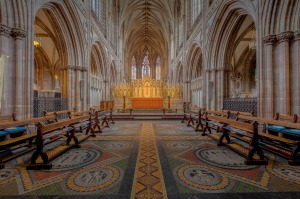 Interior of Lichfield Cathedral. Stone arches flank an elaborately tiled floor.
