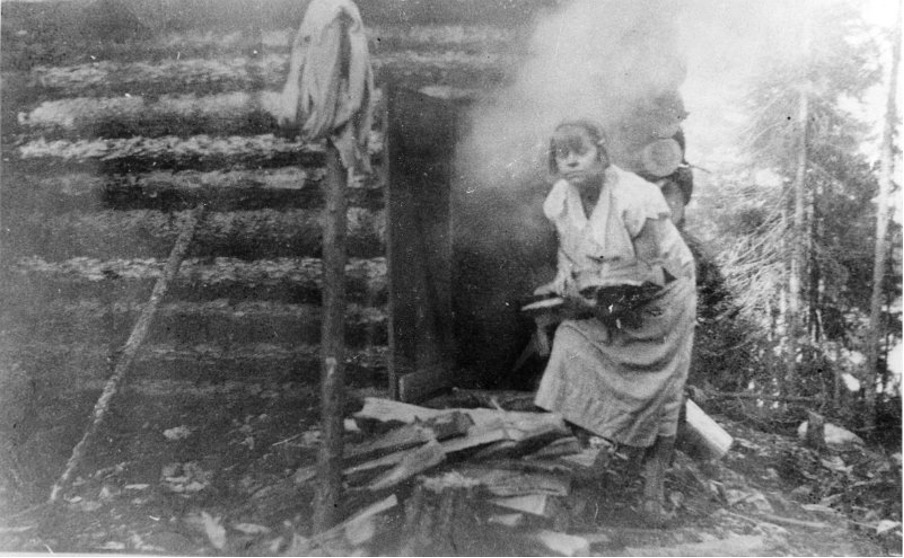 Black and white photograph of a woman loading wood into a sauna. She wears a simple dress. There are pine trees in the background.