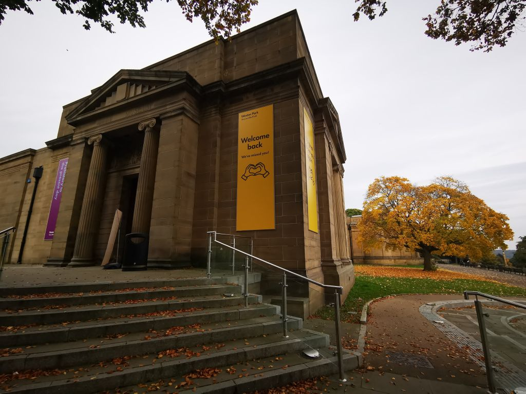 Shieffled's Weston Park Museum. A large stone building, fronted by column and accessed via raised steps. The scene is autumnal.