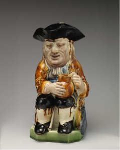 Image of a Toby Jug. The jug is shaped like a man in black, three-corner hat. He holds a beer jug and looks a bit drunk!