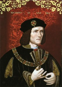 Portrait of Richard III. A man in black velvet and gold trimmed robes. He has a pale face and shoulder-length dark hair. He stands before a red background.